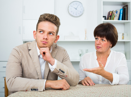 Elderly woman tries to persuade young man dont worry Stock Photo