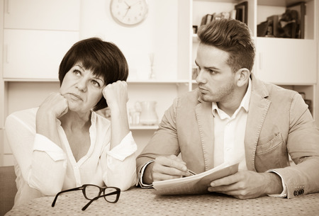 Elderly woman has discontentedly turned away from man who suggests her to sign documents Stock Photo