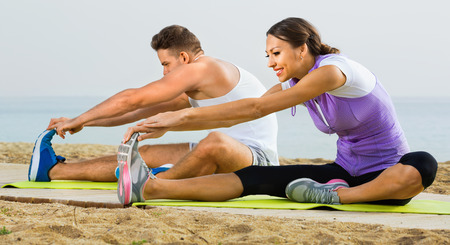 early 30s: Positive smiling couple do exercises on beach by ocean at daytime