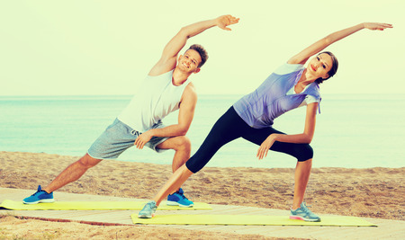 Young cheerful positive couple do exercises on beach by ocean at daytime