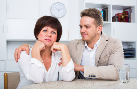 Young son calms upset elderly mother Stock Photo