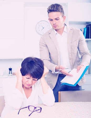 Senior mother was has turned away from the son who suggests her to sign documents Stock Photo