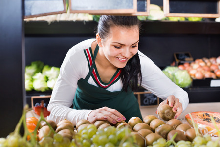 Young happy cheerful positive female shop assistant sorting kiwis in grocery shop