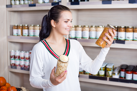 Smiling girl deciding on canned beans at grocery shop