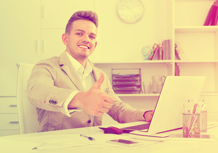alright: Portrait of happy smiling businessman showing thumbs up in modern office