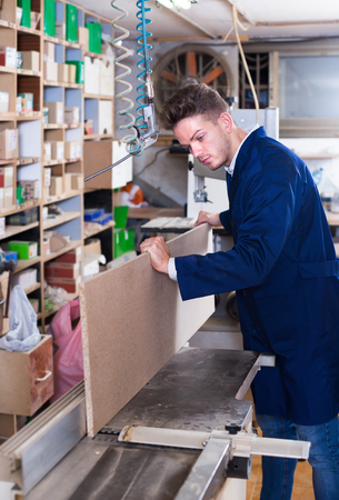to mend: Young male woodworker adjusting chipboard at workplace Stock Photo