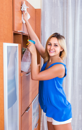 doing chores: Ordinary smiling blonde girl in blue blouse dusting furniture indoors Stock Photo