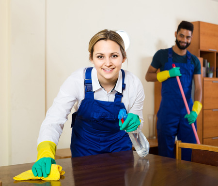 office cleanup: smiling interracial professional couple in uniform cleaning at domestic interior