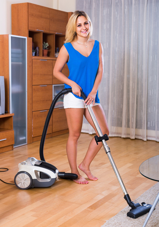 adult russian maid using modern hoover during clean-up indoors