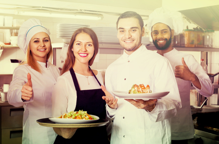 food stuff: happy waitress and crew of professional cooks posing at restaurant kitchen