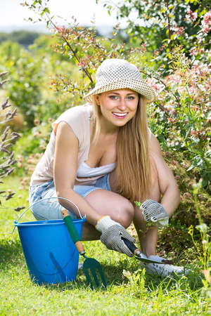 portrait of cheerful female gardener sitting and planting flowers in yard