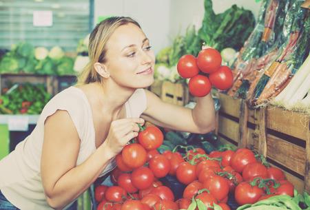Retrato, de, jovem, positivo, contente, mulher, comprando, tomates orgânicos, em, loja