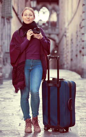 astonish: Young happy positive girl taking picture with camera in the town Stock Photo