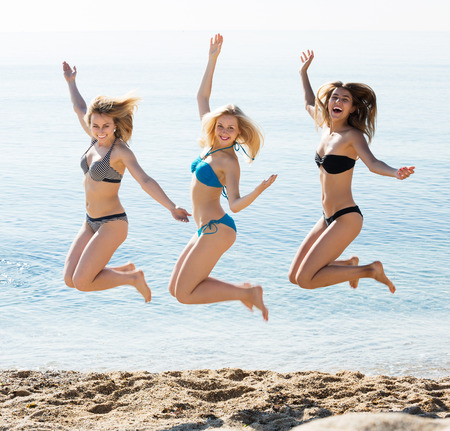 Three young happy girls wearing swimwear jumping on beach together. Focus on left girl