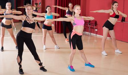 Portrait of happy fitness girls practicing zumba in modern dance class