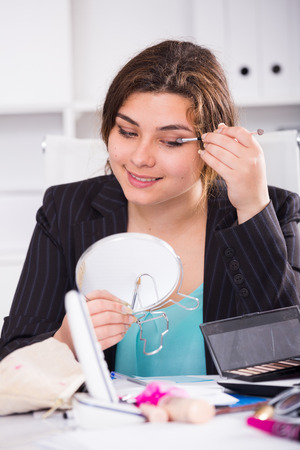 Young businesswoman is preparing herself for meeting in office. Stock Photo