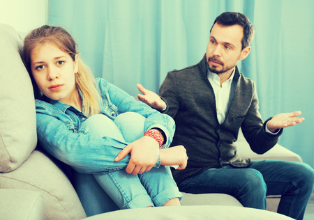 Young father arguing with his teenage daughter at home Stock Photo