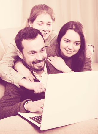 booked: positive russian family members enjoying booking hotel online on laptop together at home Stock Photo