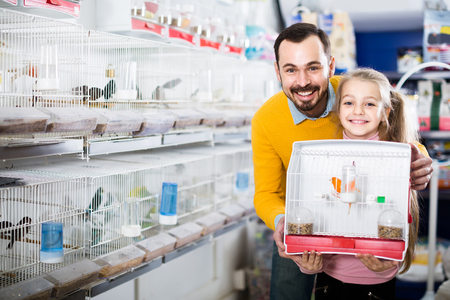 boasting: smiling european father and daughter enjoying their purchase of canary bird in pet shop