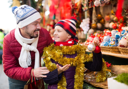 Happy man with small daughter chooses holidays decorations for Christmas outdoors Stock Photo