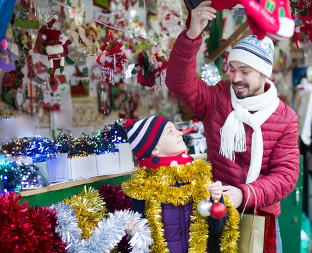 overspending: Cheerful father and child at counter with Christmas gifts in Christmas market Stock Photo