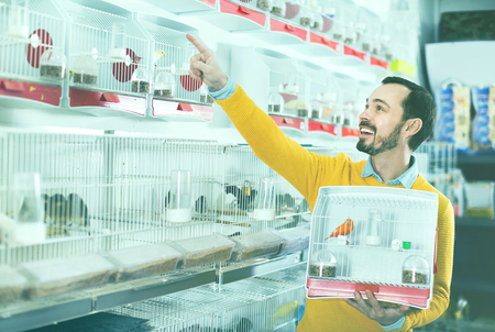 Young happy cheerful  male customer boasting his purchase of canary bird in pet shop