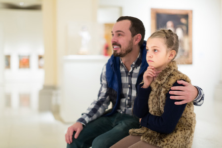 Smiling father and small daughter looking art paintings in halls of museum Reklamní fotografie - 81020659