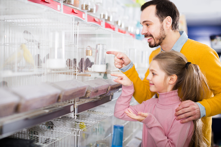 Young father showing his daughter's little birds in the store