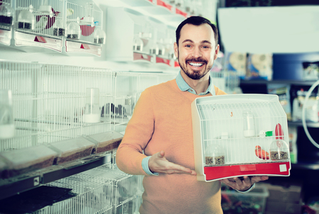 boasting: Young positive man enjoying his purchase of canary bird in pet shop Stock Photo