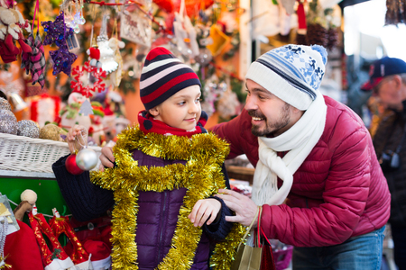 overspending: Positive dad with little daughter are smiling and choosing decorations.