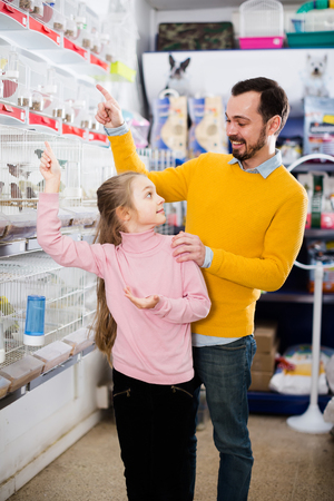 Young father with little girl looking at the birds in the pet store