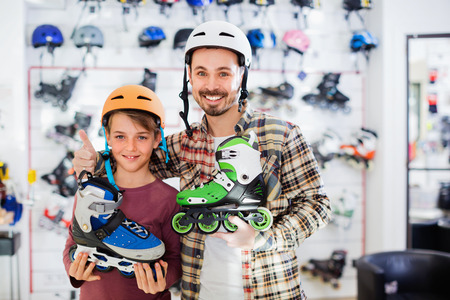 boasting: Happy cheerful father and son enjoying purchased roller-skates in sports store Stock Photo