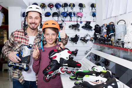 boasting: Young father and son boasting purchased roller-skates in sports store