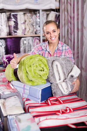 boasting: Young woman shopper buying new blanket and coverlet in textile shop