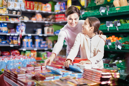sorts: Young smiling cheerful woman customer with girl looking for tasty cookies in supermarket