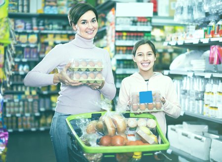 woman with daughter choosing healthy eggs in supermarket Stock Photo