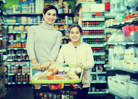 Young woman with daughter shopping with shopping cart in supermarket Stock Photo