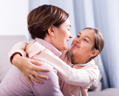 Teenage daughter asks for forgiveness and reconciled with her mother after quarrel Stock Photo