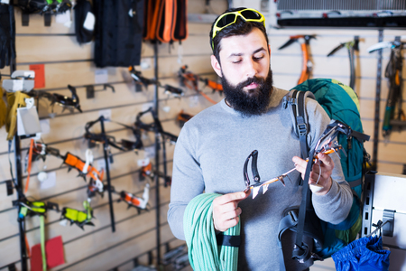 crampon: Young man selecting climbing equipment in sports equipment store