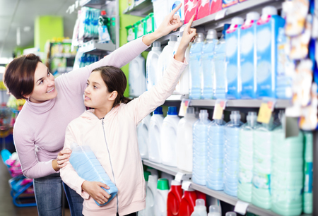 Young woman customer with girl looking for a cleaners for home in supermarket. Focus on child Stock Photo