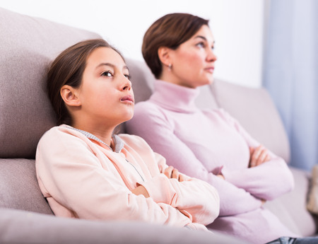 Young mother and daughter take offense at each other because of quarrel Stock Photo