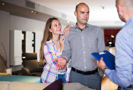 25s: Couple choosing furniture for apartment in salon with help of salesman Stock Photo
