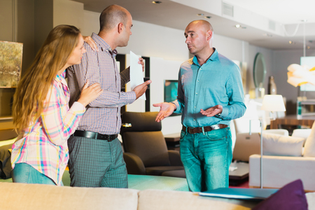 furor: Disgruntled family couple communicating with furniture seller about poor-quality service Stock Photo