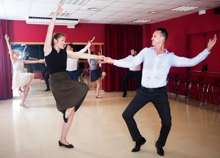 Happy adult dancing couples enjoying active boogie-woogie in modern studio
