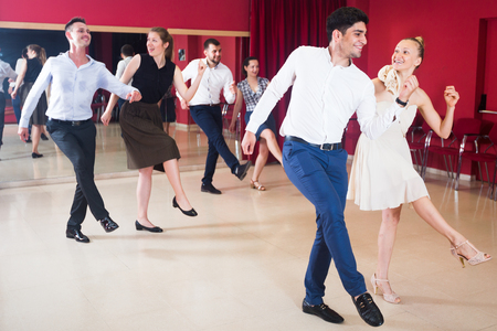25s: Young smiling people practicing vigorous jive movements in dance class