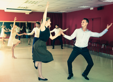 Adult people dancing lindy hop in pairs in dance hall Stock Photo