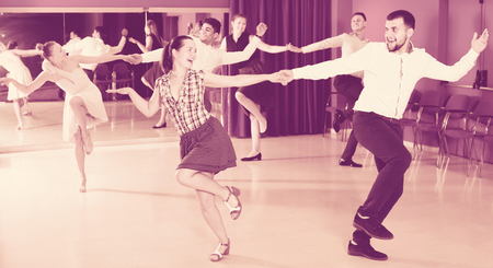 Ordinary group people dancing lindy hop in pairs in dance hall Stock Photo