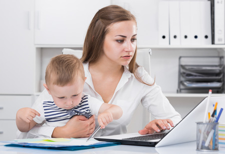 Serious mother with kid is ?oncentratedly working behind laptop in office.