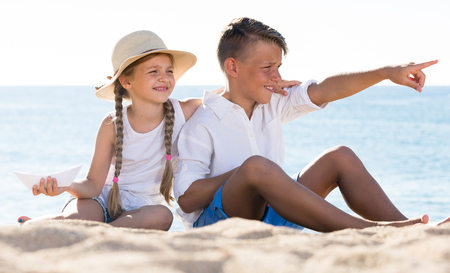 two smiling children in elementary school age looking aside and pointing with finger on beach