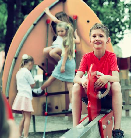 joyful  boy in elementary school age riding toy on childrens playground